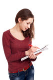 Female student writing on clipboard Royalty Free Stock Images