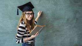 Female student writing on green chalkboard royalty free stock photography