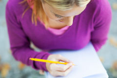 Female student writing in notebook Stock Photo