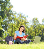 Female student writing in a notebook outdoors Stock Image