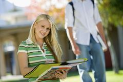 Female Student Writing Notes. Portrait of happy female student writing notes with men standing in the background Royalty Free Stock Image
