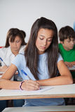Female Student Writing Paper At Desk In Classroom Stock Photography