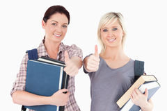 Female students with books and thumbs up Royalty Free Stock Image