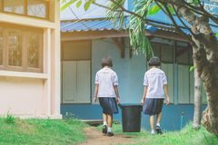 Female Students help to remove rubbish from the classroom
