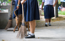 Female students help to sweep the concrete floor with a broom