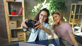 Female students are making selfie with camera while sitting together at table in modern office. They are posing, smiling. Cheerful female students are making stock footage