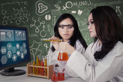 Female students mix the chemical fluid Royalty Free Stock Photography