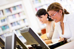 Female students researching at the library Royalty Free Stock Images