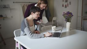 Female students searching internet on laptop computer. Two woman looking news. In laptop computer at home room. Young woman working on notebook at table stock footage