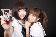 Female students self-portrait. Two Asian female students in uniform taking self-portrait on dark royalty free stock images