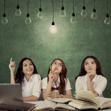 Female students sit under light bulb. Three beautiful female high school students studying together while thinking idea and sitting under light bulb Stock Photography