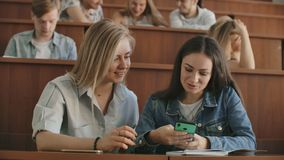 Female students with a smartphone in their hands laughing in the audience during a break for a lecture at the University.  stock video