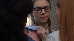 Female students stopping girl in schoolyard, demonstrating authority, bullying. Stock footage stock video