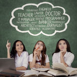 Female students thinking their dreams job. Three female high school students sitting in the class while thinking their dreams job on speech bubble Royalty Free Stock Images