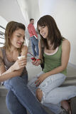 Female Students Using Mobile Phone On Stairs Royalty Free Stock Photos