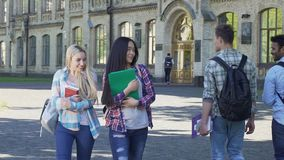 Female students walking near university and smiling to men. Flirt. Slow-motion. Stock footage stock footage