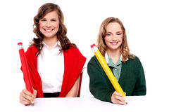 Female students writing with big pencil Stock Photography