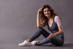 Female studio shooting. Portrait of a young beautiful woman full-length sitting on the floor on a gray background and a smile to the camera royalty free stock photos