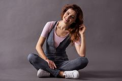 Female studio shooting. Portrait of a young beautiful woman full-length sitting on the floor on a gray background and a smile to the camera royalty free stock images