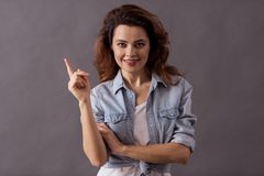 Female studio shooting. Portrait of a young beautiful woman on a gray background holding an index finger up and a smile to the camera stock images