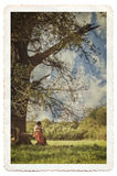 Female studying a book under a tree. Female reading book under tree, vintage photograph look. Textured, gritty detail with soft focus, cracks and borders Royalty Free Stock Photo
