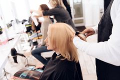 Female stylist combs blond straight hair of mature woman in beauty salon. stock photography