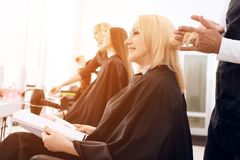 Female stylist combs blond straight hair of mature woman in beauty salon. royalty free stock image