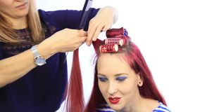 Female stylist creating perfect hairstyle with large curls for young redhead woman.  stock video footage
