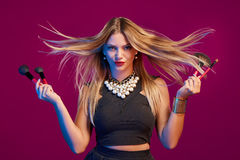 Female stylist with hair flying holding makeup brushes Stock Photo