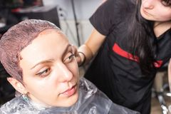 Female stylist wiping off the remains of paint with a cotton dis. C from the head of young women while she is sitting in hairdresser armchair in beauty salon Stock Photography