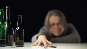 Female suffering alcohol poisoning trying to reach phone to call for help, aid. Stock footage stock footage