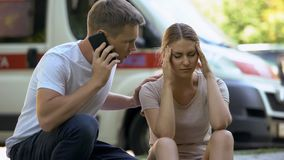Female suffering headache, not indifferent man calling ambulance, first aid royalty free stock photo