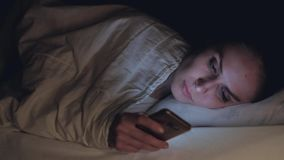 Woman use of mobile phone and lying on bed at night. Female suffering from insomnia lying in bed surfing the Internet using a smartphone at night. Slowmotion stock video