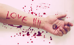 Female suicide with love messages , Knife and a ring on the hand Royalty Free Stock Images
