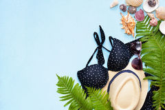 Female summer bikini swimsuit and accessories collage on blue with palm branches, hat and sunglasses. Royalty Free Stock Photos