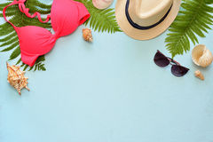 Female summer bikini swimsuit and accessories collage on blue with palm branches, hat and sunglasses. Stock Photo