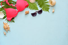 Female summer bikini swimsuit and accessories collage on blue with palm branches, hat and sunglasses. Royalty Free Stock Photo