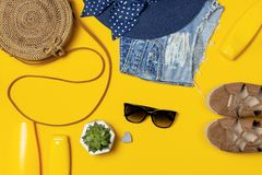 Female summer fashion background. Clothes and accessories on yellow background. Blue hat, denim shorts, round rattan bag, sandals. Sunglasses, sunscreen. Flat royalty free stock photo
