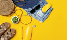 Female summer fashion background. Clothes and accessories on yellow background. Blue hat, denim shorts, round rattan bag, sandals. Sunglasses, sunscreen. Flat stock photo