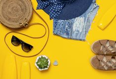 Female summer fashion background. Clothes and accessories on yellow background. Blue hat, denim shorts, round rattan bag, sandals. Sunglasses, sunscreen. Flat stock photography