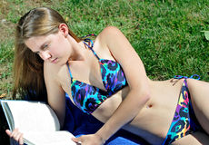 Female sunbather reading in a bikini Royalty Free Stock Images