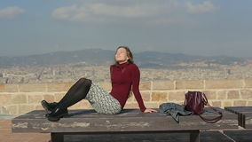 Female sunbathing on a bench at top point of city. Legs on bench stock footage