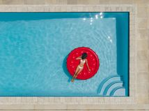 Female sunbathing on floating mattress in pool. Top view of woman relaxing on a inflatable mattress in swimming pool with her face covered with hat. Female in Royalty Free Stock Photography