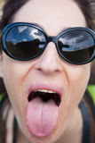 Female with sunglasses sticking out her tongue. Close-up of face brunette woman with black sunglasses looking and teasing sticking-out tongue to camera royalty free stock photos