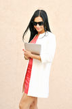 Female in sunglasses using tablet pc. Outdoors stock photo