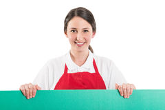 Female supermarket employee holding green board Royalty Free Stock Photography