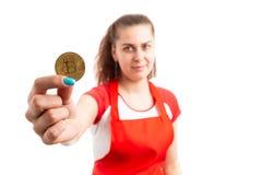 Female supermarket or hypermarket employee holding bitcoin symbol. Young female supermarket or hypermarket employee holding bitcoin symbol as cryptocurrency royalty free stock image