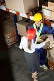 Female Supervisor Communicating With Foreman. High angle view of female supervisor communicating with young foreman at warehouse Royalty Free Stock Photo