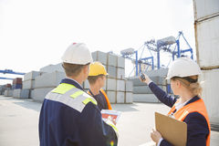 Female supervisor discussing with workers in shipping yard Stock Photo