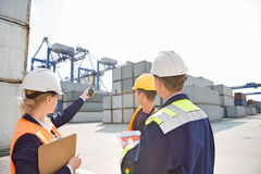Female supervisor discussing with workers in shipping yard Royalty Free Stock Images